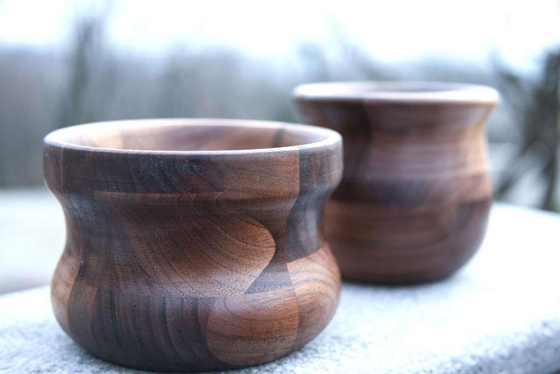 Leseni časi iz več koščkov lesa, postavljeni ena pred drugo na zunanji polici.