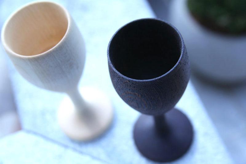 Okrasna lesena kozarca, črne in bele barve, postavljena drug poleg drugega.