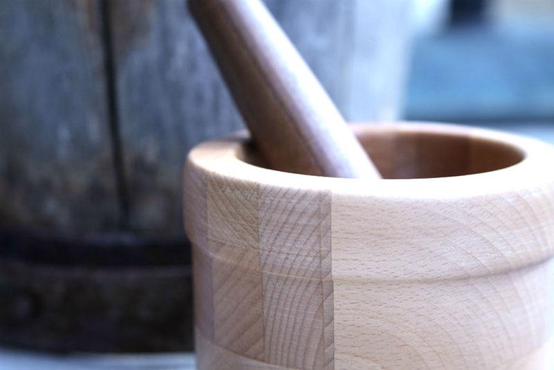 Leseni možnar s terilnikom, slikan od blizu poleg lesenega soda.