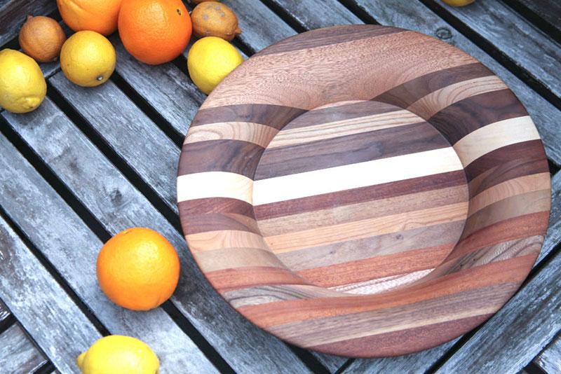 Leseni pladenj, sestavljen iz raznobarvnih kosov lesa, ki tvorijo progast vzorec, postavljen na mizo, na kateri so tudi pomaranče in limone.