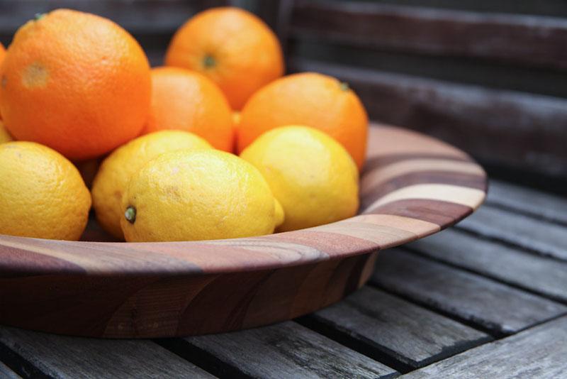 Okrasna lesena skleda s pomarančami in limonami na leseni mizi.