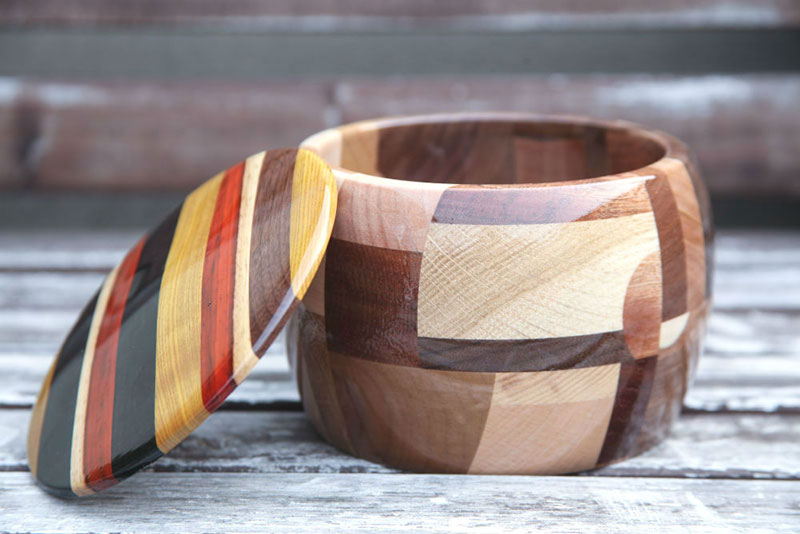 Leseni izdelek je odprta skleda, na katero je naslonjen prilegajoči pokrov.