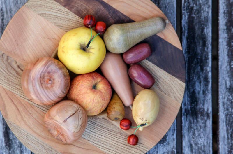 Leseno in pravo sadje na lesenem pladnju.