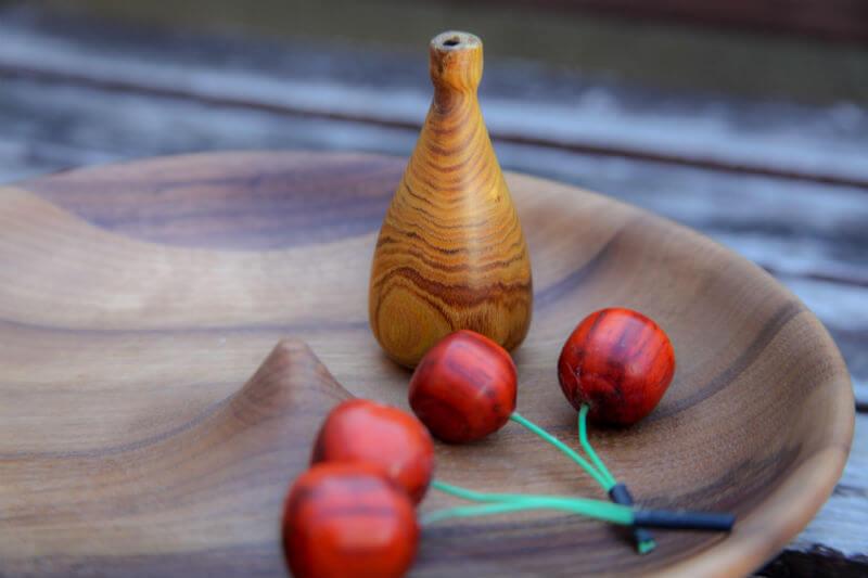 Rdeče dekorativne lesene češnje na lesenem pladnju.